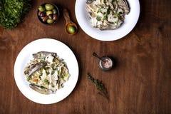 Tagliatelle med kronärtskockor och tioarmade bläckfisken i kräm- sås royaltyfri foto