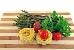 Tagliatelle mit wildem Spargel und roten Tomaten Lizenzfreie Stockbilder