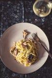 Tagliatelle- och bläckfiskmaträtt, vitt vin åt sidan fotografering för bildbyråer
