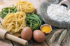 Tagliatelle och ingredienser med bakgrund Arkivbild