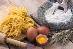 Tagliatelle och ingredienser med bakgrund Royaltyfri Foto