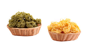 Tagliatelle paglia e fieno. At round woven straw baskets on the white background Stock Images