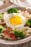 Tagliatelle pasta with broccoli, prosciutto and fried egg. Royalty Free Stock Photography