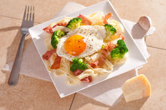Tagliatelle pasta with broccoli, prosciutto and fried egg. Stock Photo