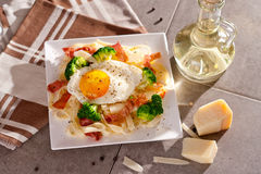 Tagliatelle pasta with broccoli, prosciutto and fried egg. Royalty Free Stock Images