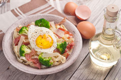 Tagliatelle pasta with broccoli, prosciutto and fried egg. Stock Photos