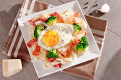 Tagliatelle pasta with broccoli, prosciutto and fried egg. Royalty Free Stock Image