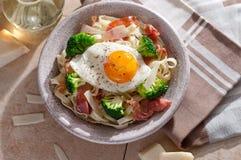 Tagliatelle pasta with broccoli, prosciutto and fried egg. Stock Photo