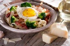 Tagliatelle pasta with broccoli, prosciutto and fried egg. Stock Image