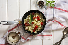 Tagliatelle Pasta with cherry tomatoes in a pan  white wooden table and red checkered tablecloth Stock Image