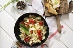 Tagliatelle Pasta with cherry tomatoes in a pan  white wooden table and red checkered tablecloth Stock Photography