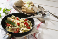 Tagliatelle Pasta with cherry tomatoes in a pan  white wooden table and red checkered tablecloth Stock Images