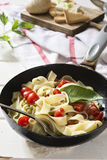 Tagliatelle Pasta with cherry tomatoes in a pan  white wooden table and red checkered tablecloth Royalty Free Stock Image