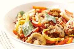 Tagliatelle pasta with chicken mushrooms, red pepper and onion. royalty free stock image