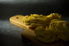 Tagliatelle pasta on a chopping board. Some raw tagliatelle pasta on a chopping board, dark mood Royalty Free Stock Photos