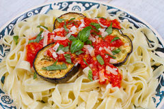 Tagliatelle pasta with grilled eggplant, spicy tomato sauce and parmesan cheese. Stock Photography