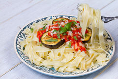 Tagliatelle pasta with grilled eggplant, spicy tomato sauce and parmesan cheese. Stock Photo