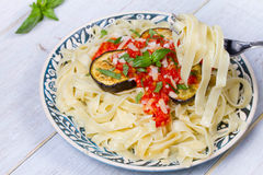 Tagliatelle pasta with grilled eggplant, spicy tomato sauce and parmesan cheese. Stock Photos