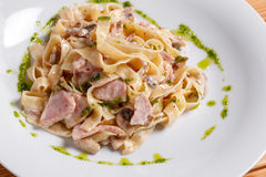 Tagliatelle pasta with ham, mushrooms and yolk. Selective focus. Pasta Carbonara on white plate with parmesan. Italian psta food concept. on a white plate, the Stock Images