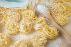 Tagliatelle pasta home made with flour and eggs. Preparation of traditional italian homemade pasta Royalty Free Stock Photos