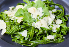 Tagliatelle pasta with parmesan cheese and arugula salad Italian cuisine on dark plate Royalty Free Stock Photos