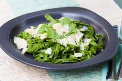 Tagliatelle pasta with parmesan cheese and arugula salad Italian cuisine on dark plate Royalty Free Stock Photo