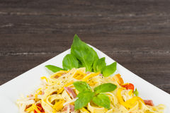 Tagliatelle pasta with pesto sauce, bacon, Gauda, Cheddar, Emmental cheese and basil leaves in white plate on grey wooden backgrou Royalty Free Stock Photo