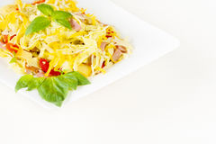 Tagliatelle pasta with pesto sauce, bacon, Gauda, Cheddar, Emmental cheese and basil leaves in white plate on white background Stock Photo