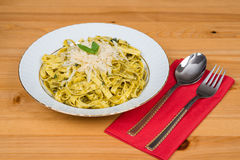 Tagliatelle pasta with pesto sauce and basil leafs on white plate, wood background. Tagliatelle pasta with pesto sauce and basil leafs on white plate Stock Photography