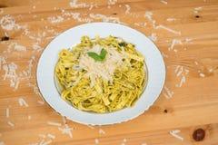 Tagliatelle pasta with pesto sauce and basil leafs on white plate, wood background. Tagliatelle pasta with pesto sauce and basil leafs on white plate Stock Photo