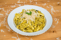 Tagliatelle pasta with pesto sauce and basil leafs on white plate, wood background Stock Image
