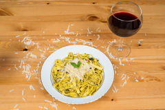 Tagliatelle pasta with pesto sauce and basil leafs on white plate, wood background. Tagliatelle pasta with pesto sauce and basil leafs on white plate with wine Royalty Free Stock Photos