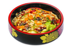 Tagliatelle pasta with smoked eel and vegetables in black bowl  on white Stock Image