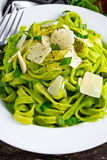 Tagliatelle pasta with spinach, avocado and parmigiano cheese, herbs in white plate. concept of healthy food Stock Photo