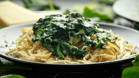 Tagliatelle pasta with spinach in cream sauce with parmesan royalty free stock photo