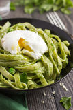 Tagliatelle pasta with spinach and green peas pesto poached egg Royalty Free Stock Image