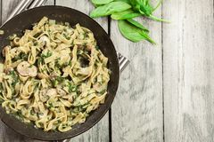 Tagliatelle pasta with spinach and mushrooms on a pan. Stock Images