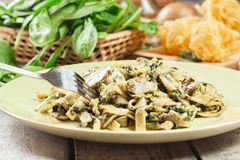 Tagliatelle pasta with spinach and mushrooms on a plate. Stock Photos