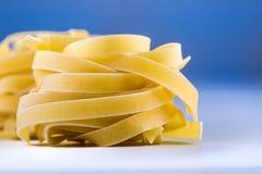 Tagliatelle pasta on white blue background.Macro concept Stock Image
