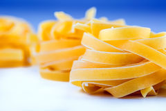 Tagliatelle pasta on white blue background.Macro concept Stock Photography