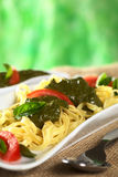Tagliatelle with Pesto. Yellow tagliatelle with fresh pesto made of basil and garlic and garnished with tomato slices and basil leaves (Selective Focus, Focus on Royalty Free Stock Photo