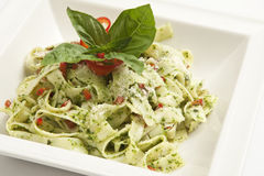 Tagliatelle with pesto sauce. On a white plate Royalty Free Stock Image