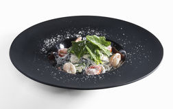 Tagliatelle with prawns in black mat plate isolated on white. Tagliatelle with shrimps and and tomatoes on a black plate decorated with parmesan isolated on stock photography