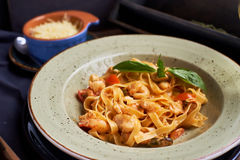 Tagliatelle with prawns and spices. Seafood pasta. Tagliatelle with prawns and spices in tomato-cream sauce. Glass of white wine Royalty Free Stock Image
