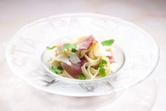 Tagliatelle with ruccolla and prosciutto. Inside, indoors, interiors, gastronomy, cuisine, food, meal, nutrition, nourishment, cooked, plate, italian, cooking stock photos