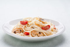 Tagliatelle sauted with tomatoes and mushrooms Stock Photo