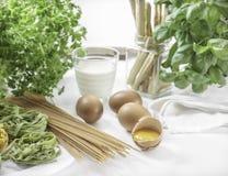 Tagliatelle, spaghetti ed uova su fondo di bicchiere di latte e delle erbe verdi Immagini Stock Libere da Diritti