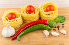 Tagliatelle with tomatoes, garlic, chili peppers and basil on bo Stock Photo