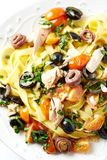 Tagliatelle with tuna, anchovy, cherry tomatoes and black olives. Top view. Vertical royalty free stock photos