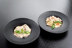 Tagliatellepasta med champinjoner och gräddost och tagliatellepasta med skaldjur arkivbild